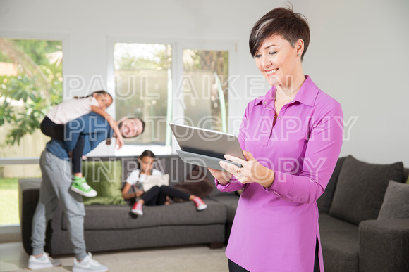 Woman watching ipad with kids at play
